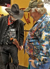 David Widdifield (left), from Noblesville, with the Single Action Shooting Society, shows his gun and holster to Joseph Kuerzi, from Clarksville, Ind., at the NRA national convention at the Indiana Convention Center on April 25, 2014.