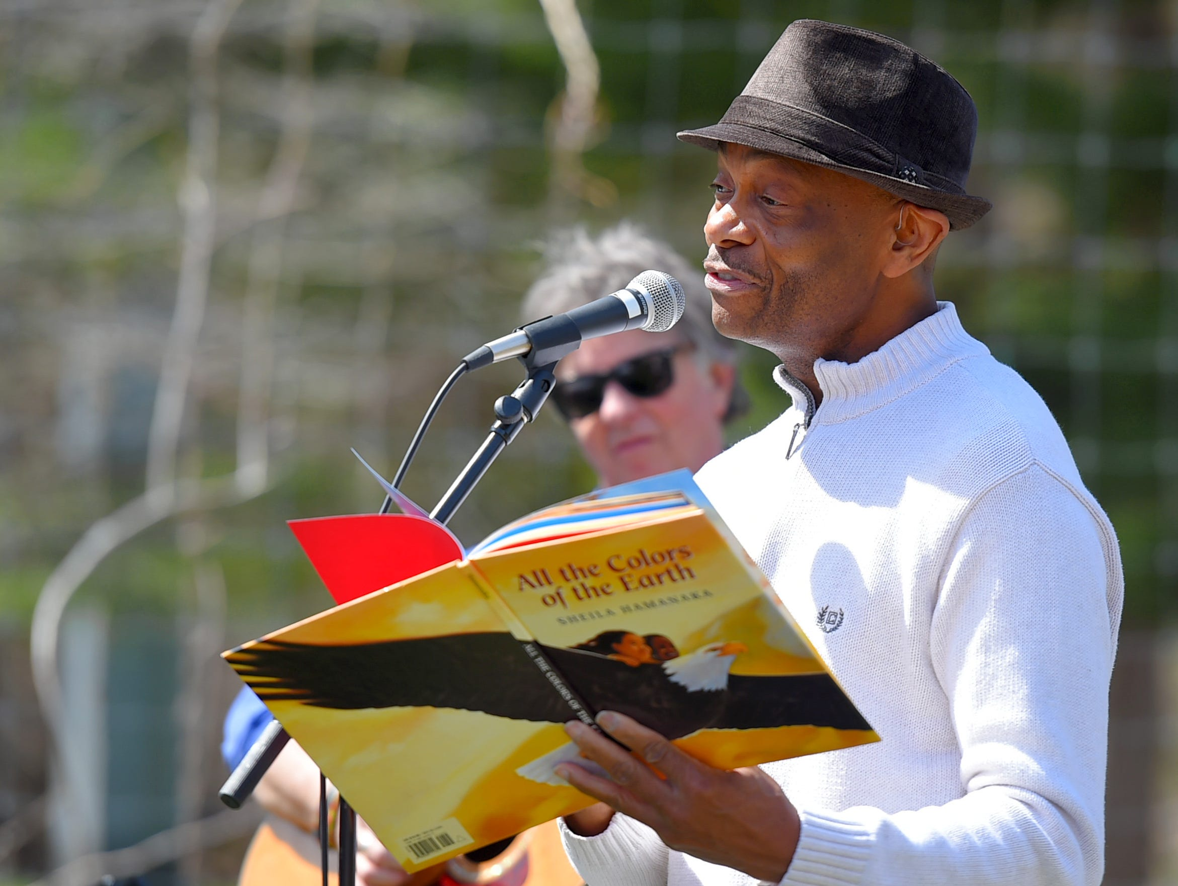 "Cal Walker reads ""All the Colors of the Earth"" during the celebration of life honoring Kathleen Downes at the Ithaca Children's Garden on April 17, 2019. Downes, a beloved Ithaca teacher, died unexpectedly last week in a car accident."