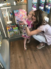 Brooke Easterwood of Madison and her daughter, Sophie, admire the selection of gifts at Brick City Drugs.