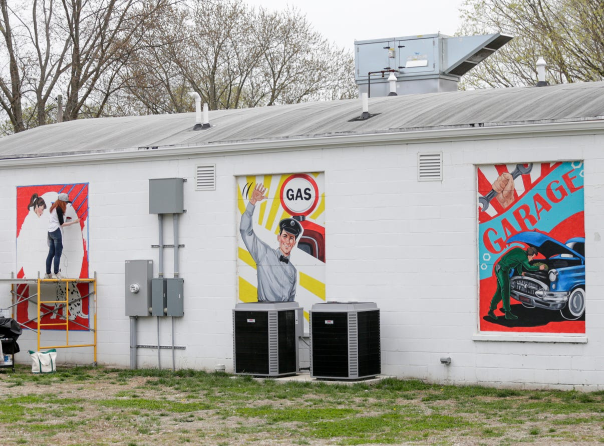 Alexandria Monik works on one of four murals on the side of Trish's Red Bird Cafe, Wednesday, April 17, 2019, in Dayton.