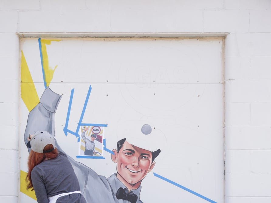 Alexandria Monik works on one of four murals on the side of Trish's Red Bird Cafe, Tuesday, April 16, 2019, in Dayton.