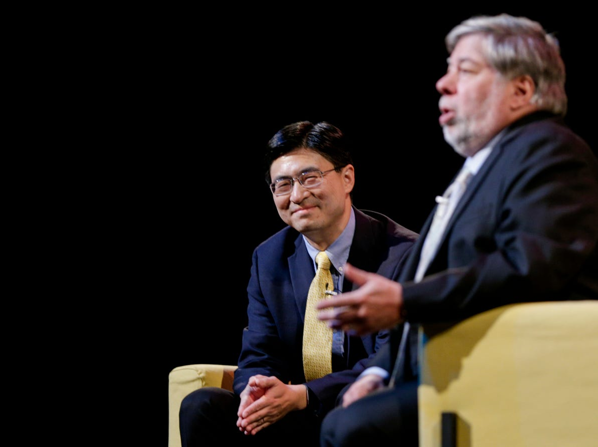 """Mung Chiang, dean of the College of Engineering, reacts as Apple co-founder Steve Wozniak speaks with speaks, Wednesday, April 17, 2019 at Purdue University's Elliott Hall of Music in West Lafayette. The talk, """"What If We Lose Control of Technology?,"""" is part of Purdue's Ideas Festival, a series of events tied to the university's 150th anniversary."""