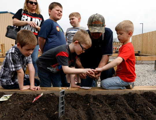 Keith Eichhorn, center, an Ohio State University Fairfield County Extension Master Gardener volunteer, holds seeds in his hand for children to plant in the raised vegetable beds Wednesday morning, April 17, 2019, at AHA! A Hands On Adventure, a Children's Museum in Lancaster. Master gardener volunteers are planting and maintaining daffodils, sunflowers and a butterfly garden in the museum's outdoor play space as well as the vegetable garden. The museum won the 2018 Ohio Museum Association Institution of the Year Award earlier this week.