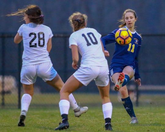 Hartland's Michelle Keranen (11) tries to kick the soccer ball past Brighton's Tara Simon (28) and Mia Hansen (10) on Tuesday, April 16, 2019.