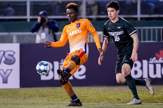 Lansing Ignite's Steeve Saint-Duc, left, kicks the ball as Michigan State's Michael Miller closes in during the second half on Tuesday, April 16, 2019, at Cooley Law School Stadium in Lansing. The Lansing Ignite won the Capital Cup 4-0.