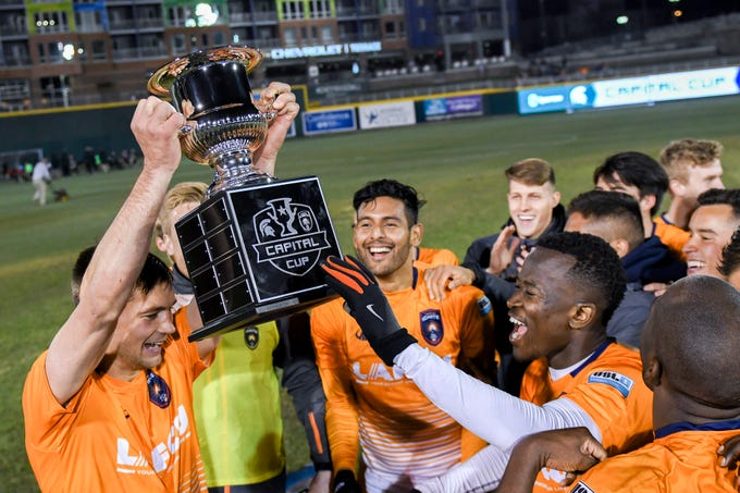 Lansing Ignite celebrates with the Capital Cup after beating  Michigan State 4-0 on Tuesday, April 16, 2019, at Cooley Law School Stadium in Lansing.