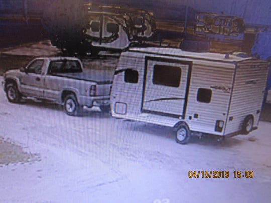 "This image taken from a surveillance camera shows a light colored GMC pickup truck taking a ""Hideout"" camper from a retail lot on Monday."