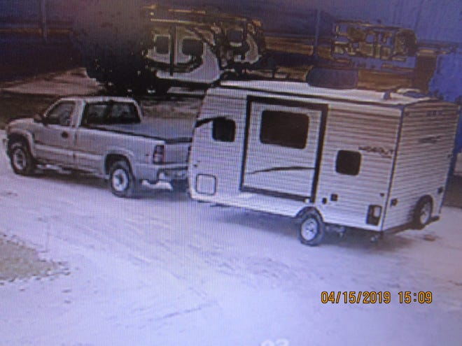 """This image taken from a surveillance camera shows a light colored GMC pickup truck taking a """"Hideout"""" camper from a retail lot on Monday."""