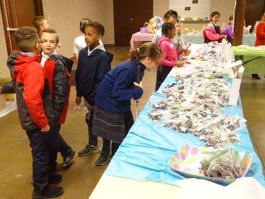 Children search through the chocolate candies for sale Wednesday at St. Peter's Easter Bake Sale.