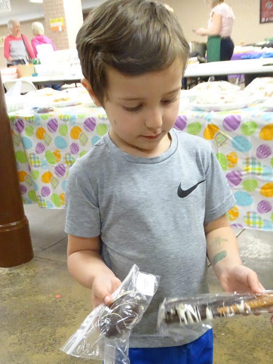 Michael Skowronski, 4, of Mansfield eyes the candy egg and chocolate-covered pretzels bought Wednesday at St. Peter's Easter Bake Sale.