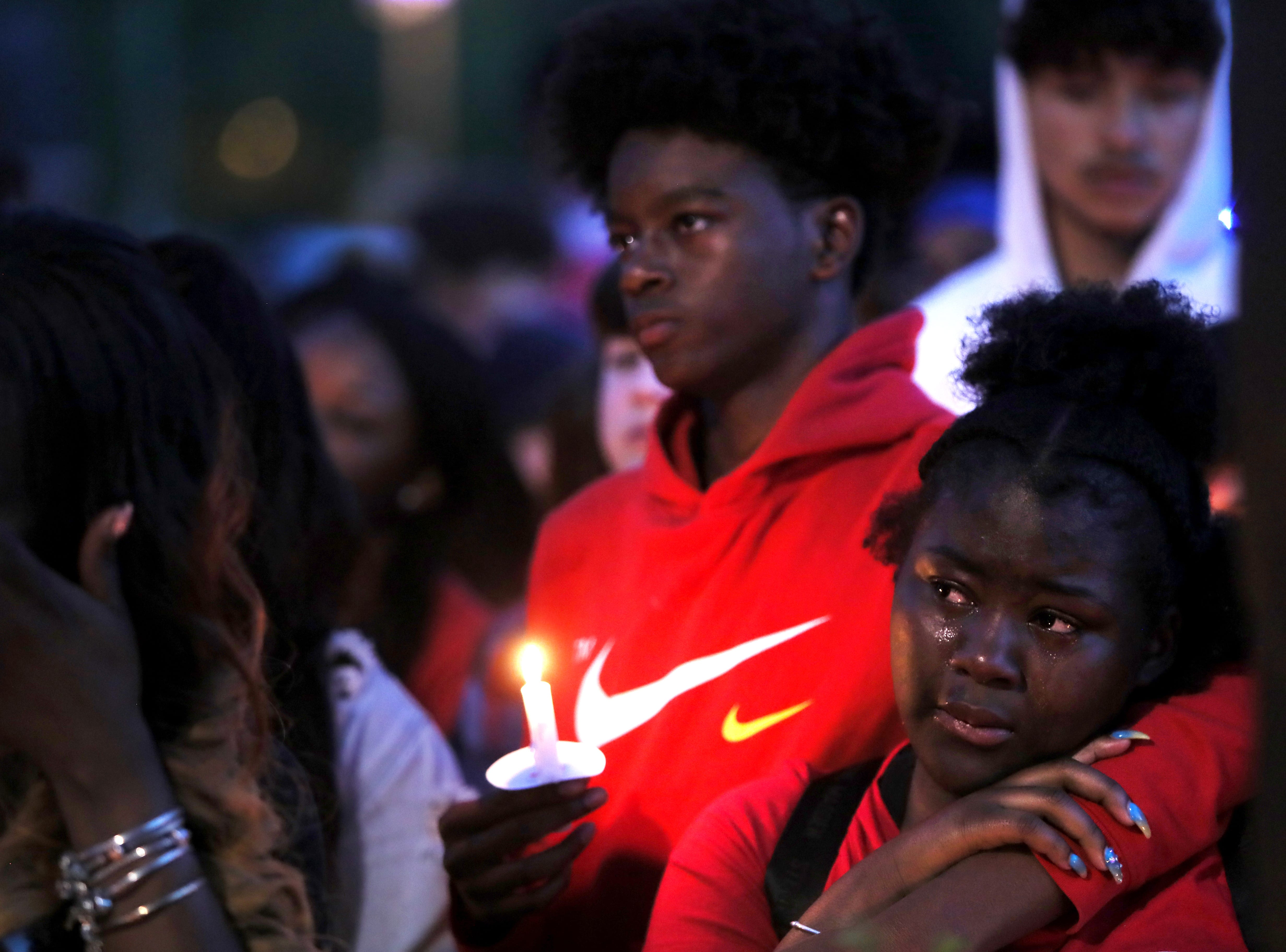 Marcus Foy consoles Skyy Bowser as they gather for a vigil Tuesday at West Junior High School in honor of former student Taylon Vail, 16, who was killed early Friday morning in a shooting at his grandparent's house where he was staying overnight.
