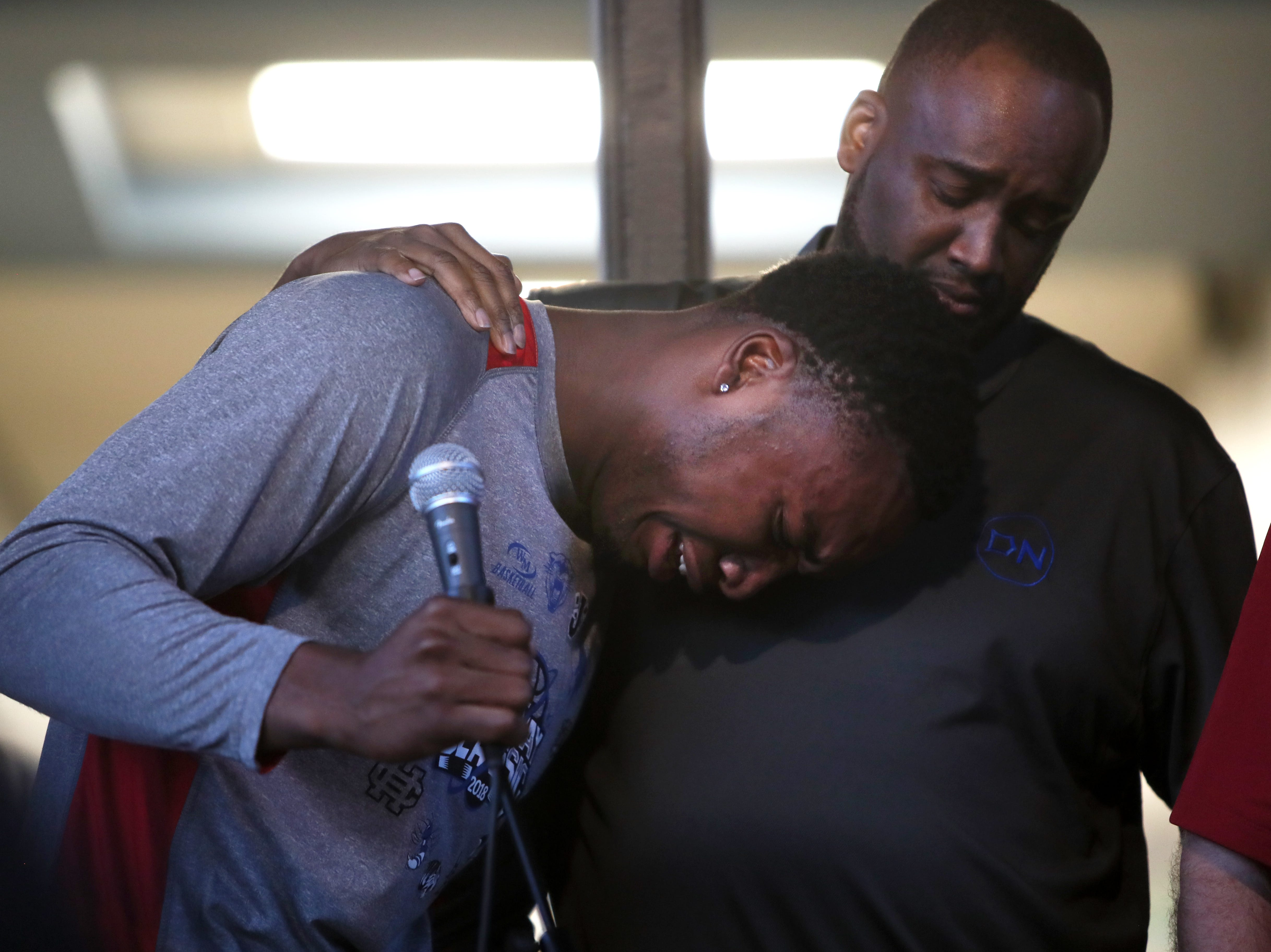Alvin Hawkins holds his younger brother Chris Moore as he breaks down while reading a poem in honor of Taylon Vail, 16, who was killed early Friday morning, during a vigil in his name held Tuesday at West Junior High.