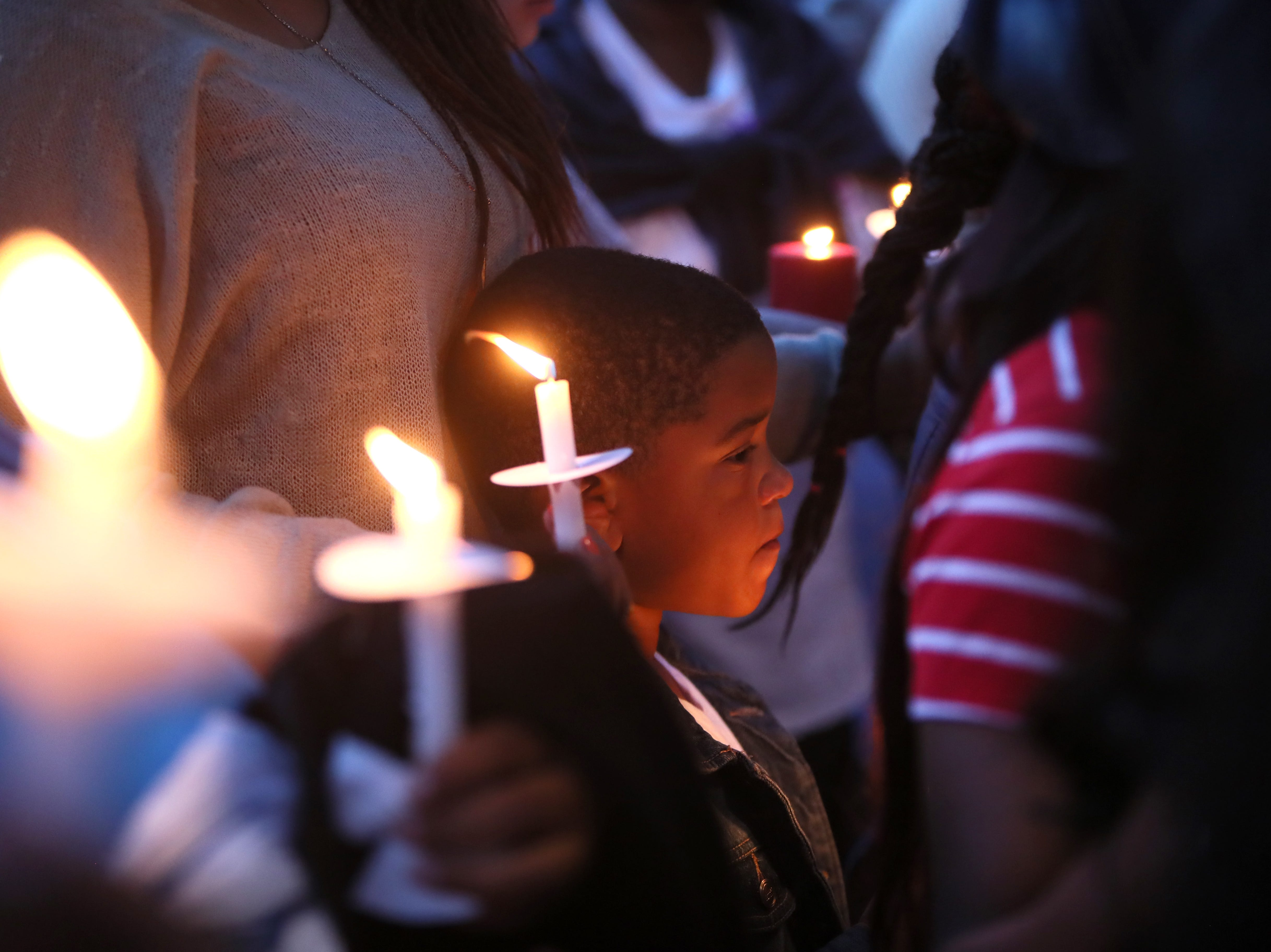 People gather for a vigil Tuesday at West Junior High School in honor of former student Taylon Vail, 16, who was killed early Friday morning in a shooting at his grandparent's house where he was staying overnight.