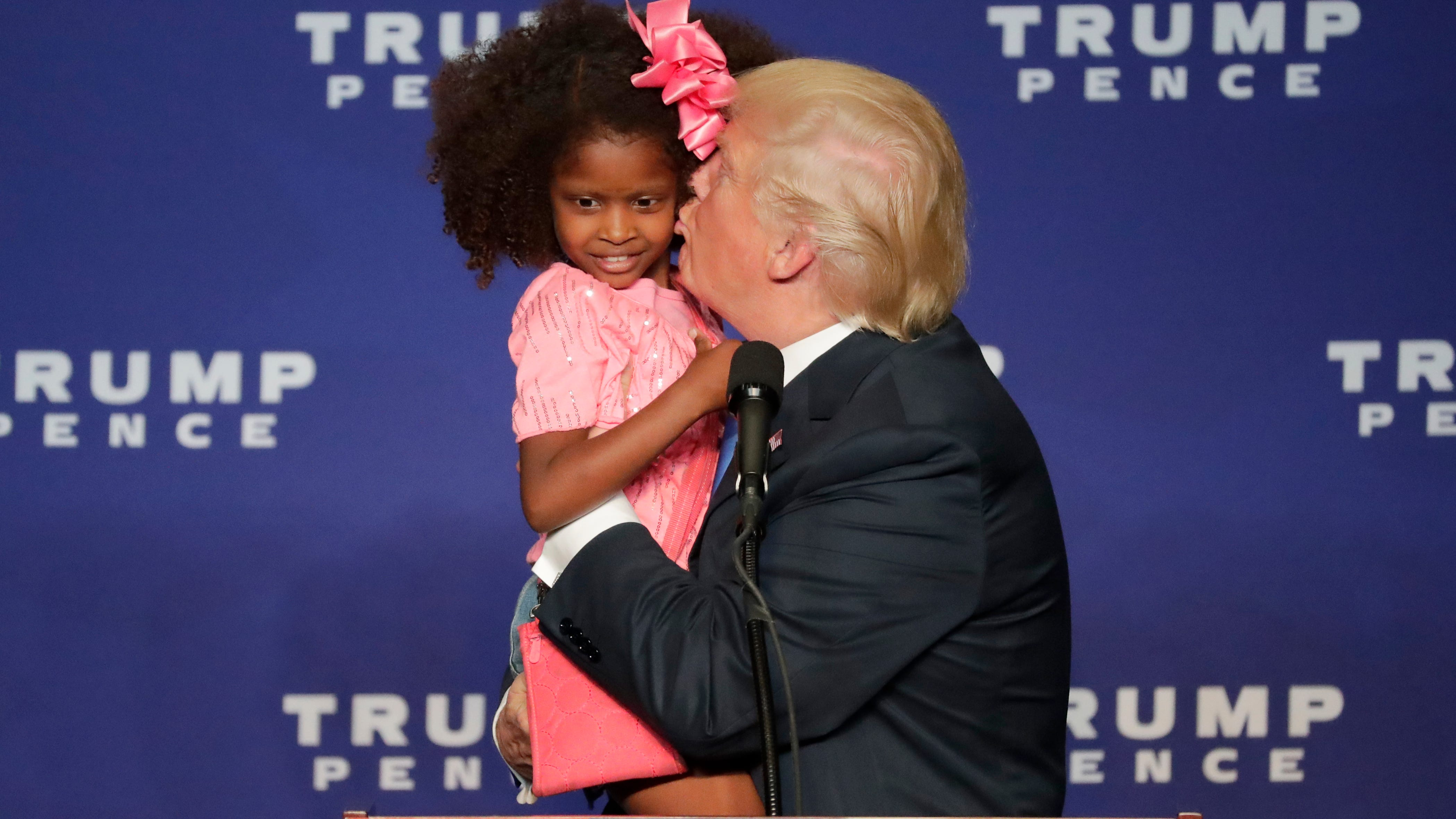 Presidential candidate Donald Trump kisses a young girl he called up onto the stage at a campaign rally at the KI Convention Center in Green Bay, October 17, 2016.