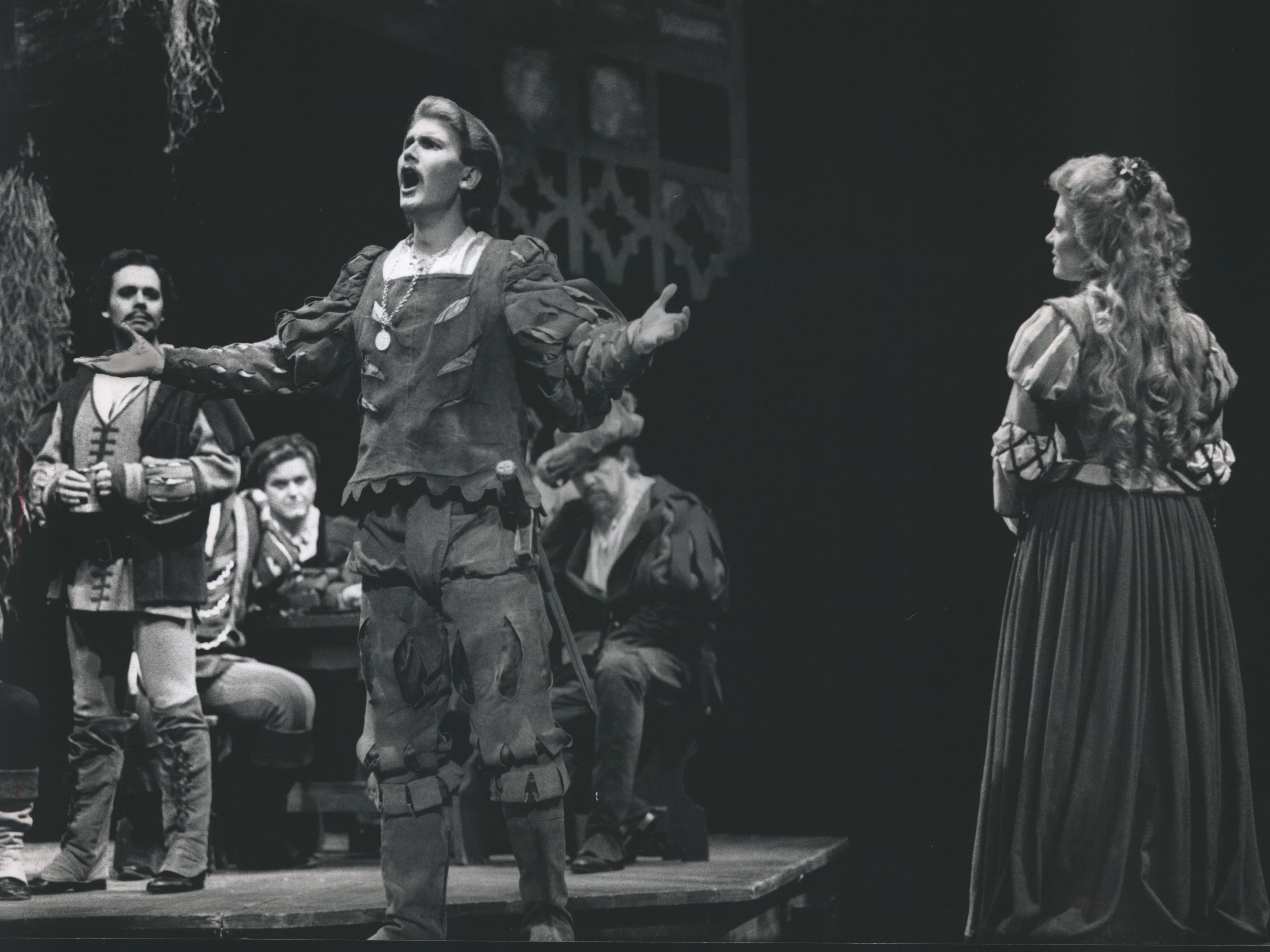 "Gordon Holleman (left), as Wagner, and Faith Esham (right), as Marguerite, listen as Patryk Wroblewski performs in the role of Valentin in the Florentine Opera production of ""Faust,"" 1989."