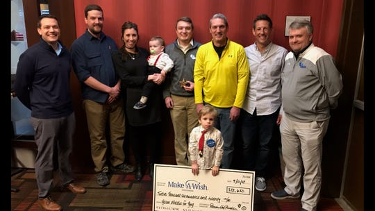 Members of the Wisconsin Basketball Officials Association celebrate Graham (with check), a 3-year-old with a heart condition after Yellow Whistles For Greg raised enough money for him to visit Disney World. Others pictured are (from left) WBOA past president Jeff Lewis, Graham's father David and mother Maeve, Bobby Von Rueden, Denny Von Rueden, Andy Gallion and Ken Koester.