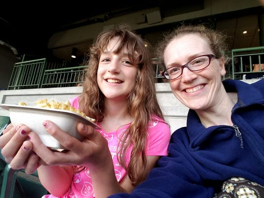 Alex Schwabe (with Amy Schwabe) enjoys her waffle fries at a peanut-controlled Brewer game.