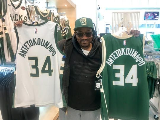 Julius Cocroft buys jerseys for his uncles who live in Chicago at the Bucks Pro Shop at Fiserv Forum.