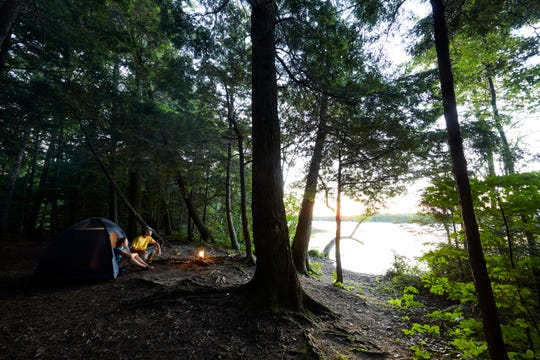 A couple relaxes at their campsite in Newport State Park.