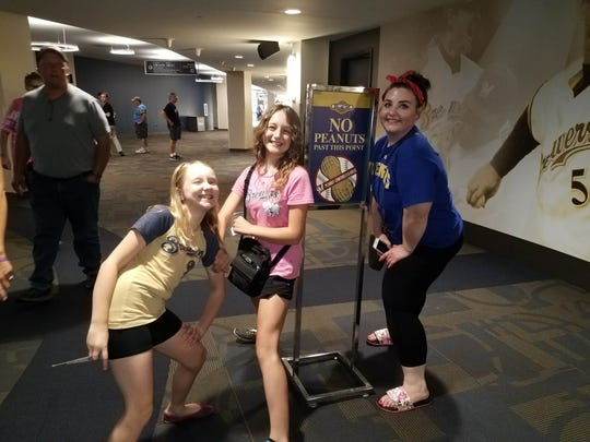 Wendy and Alex Schwabe pose with their aunt, Cassie Schwabe, in front of the peanut-controlled section at Miller Park.