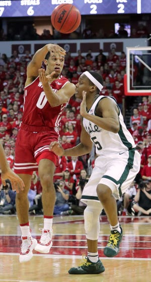 Wisconsin's D'Mitrik Trice  rifles a pass while being defended by Michigan State guard Cassius Winston during their game Feb.  at the Kohl Center in Madison.