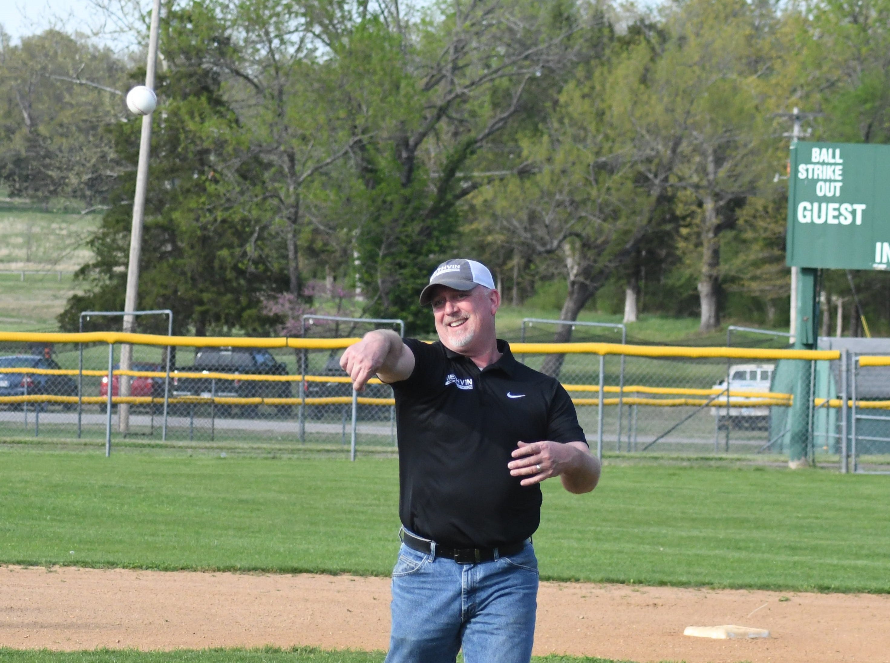 Methvin Sanitation operations manager Jay Mathis delivers the first pitch Tuesday evening at Methvin Sanitation Field at Clysta Willett Park.