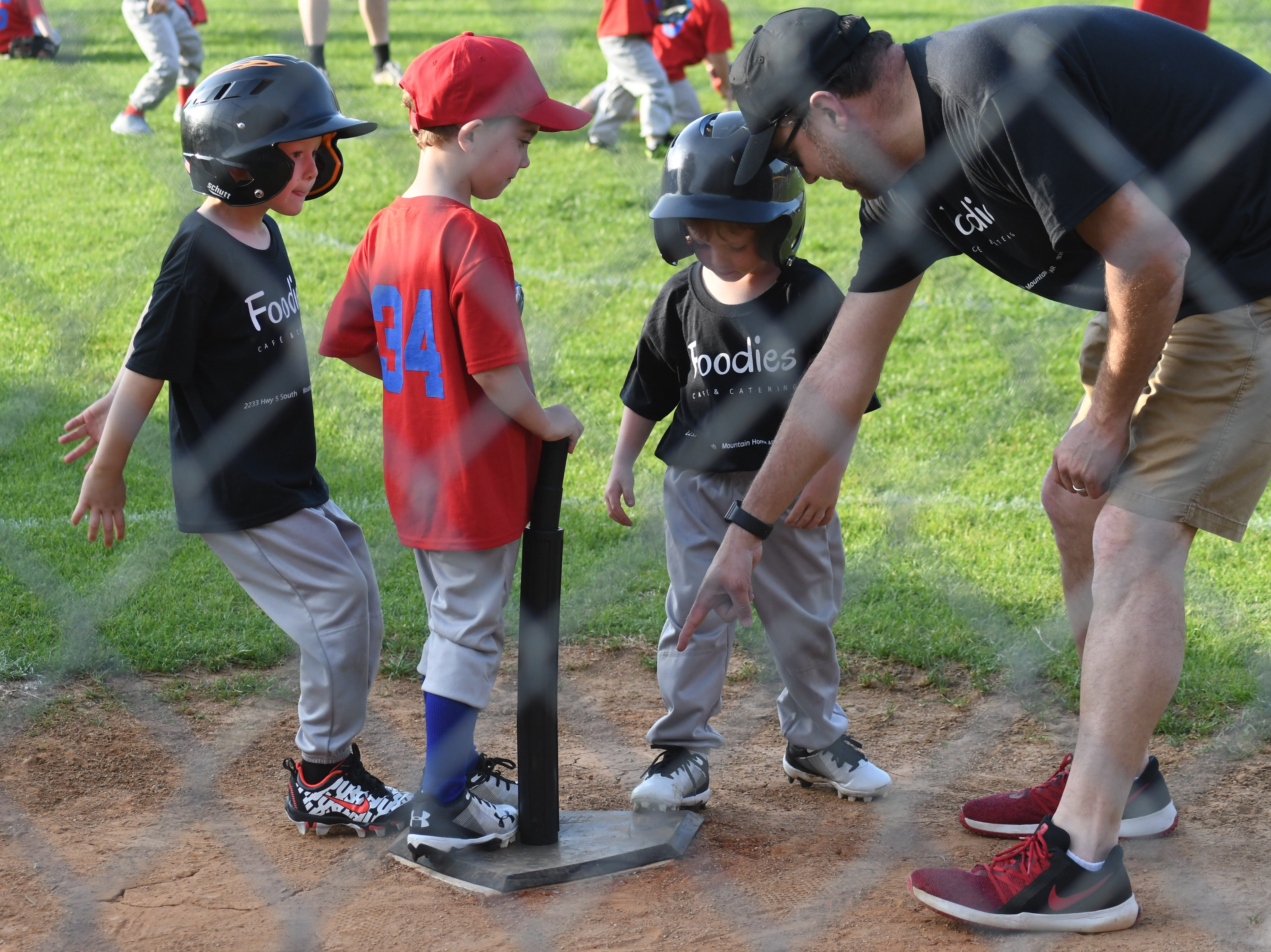 A coach for the Foodies team reminds his players to touch home plate during their game against the Baxter County Republicans on Tuesday at Sanders, Morgan & Clarke Field.