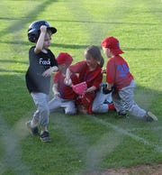 A baserunner for Foodies heads for home while a scrum for the baseball develops among the infielders for the Baxter County Republicans on Tuesday at Sanders Morgan & Clarke Field at Clysta Willett Park.