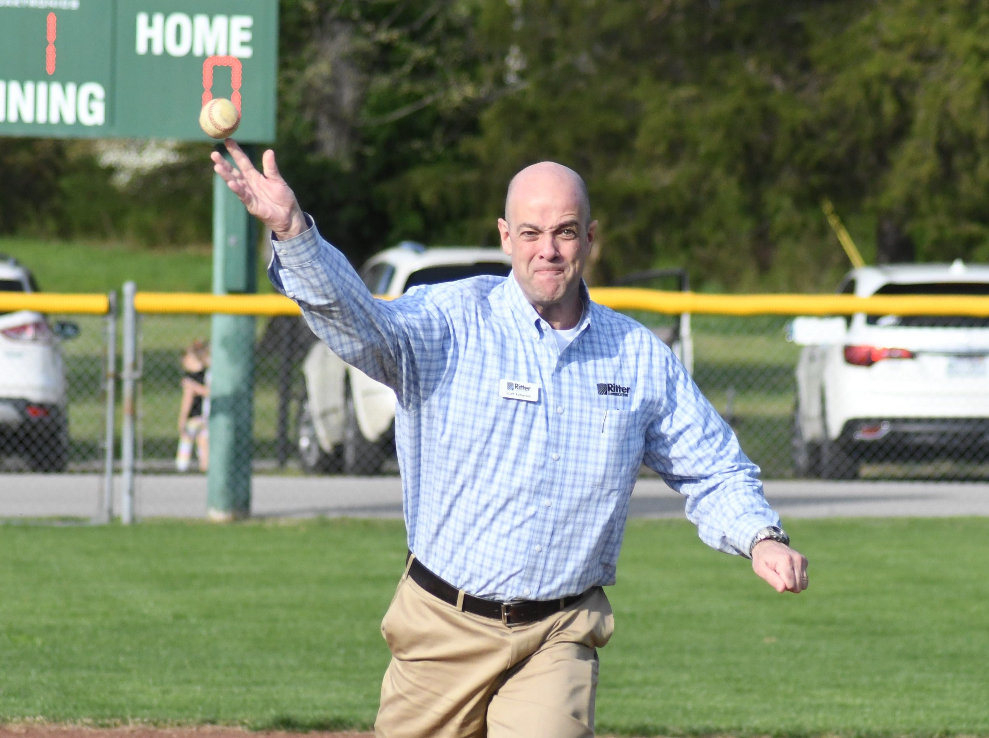 Scott Robertson, business sales representative for Ritter Communication, throws out the ceremonial first pitch at Ritter Communication Field on Tuesday evening.