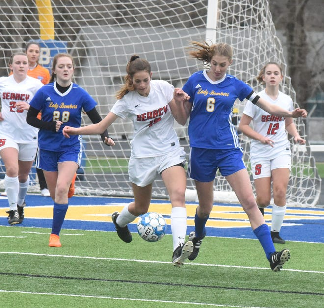Mountain Home's Chloe Nosari (6) battles a Searcy player for the ball during a match earlier this season.