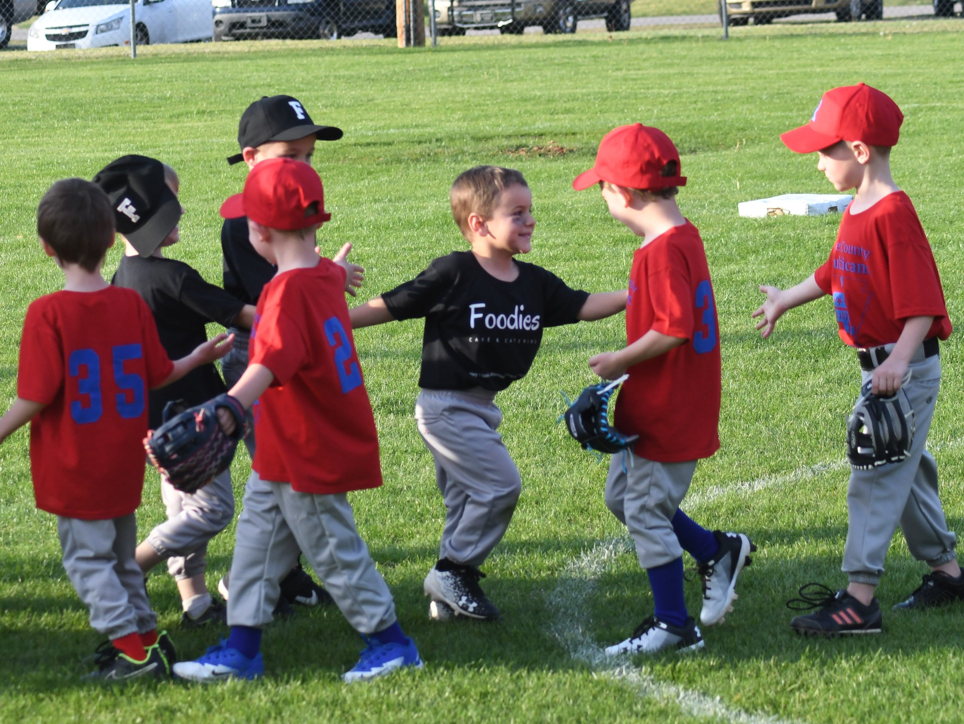 Members of the Foodies and Baxter County Republicans T-ball teams shake hands following their game Tuesday evening at Sanders, Morgan & Clarke Field.