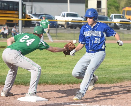 Cotter's Cole Adams gets back to first base on a pickoff attempt as Yellville-Summit's Ryan Fletcher takes the throw.