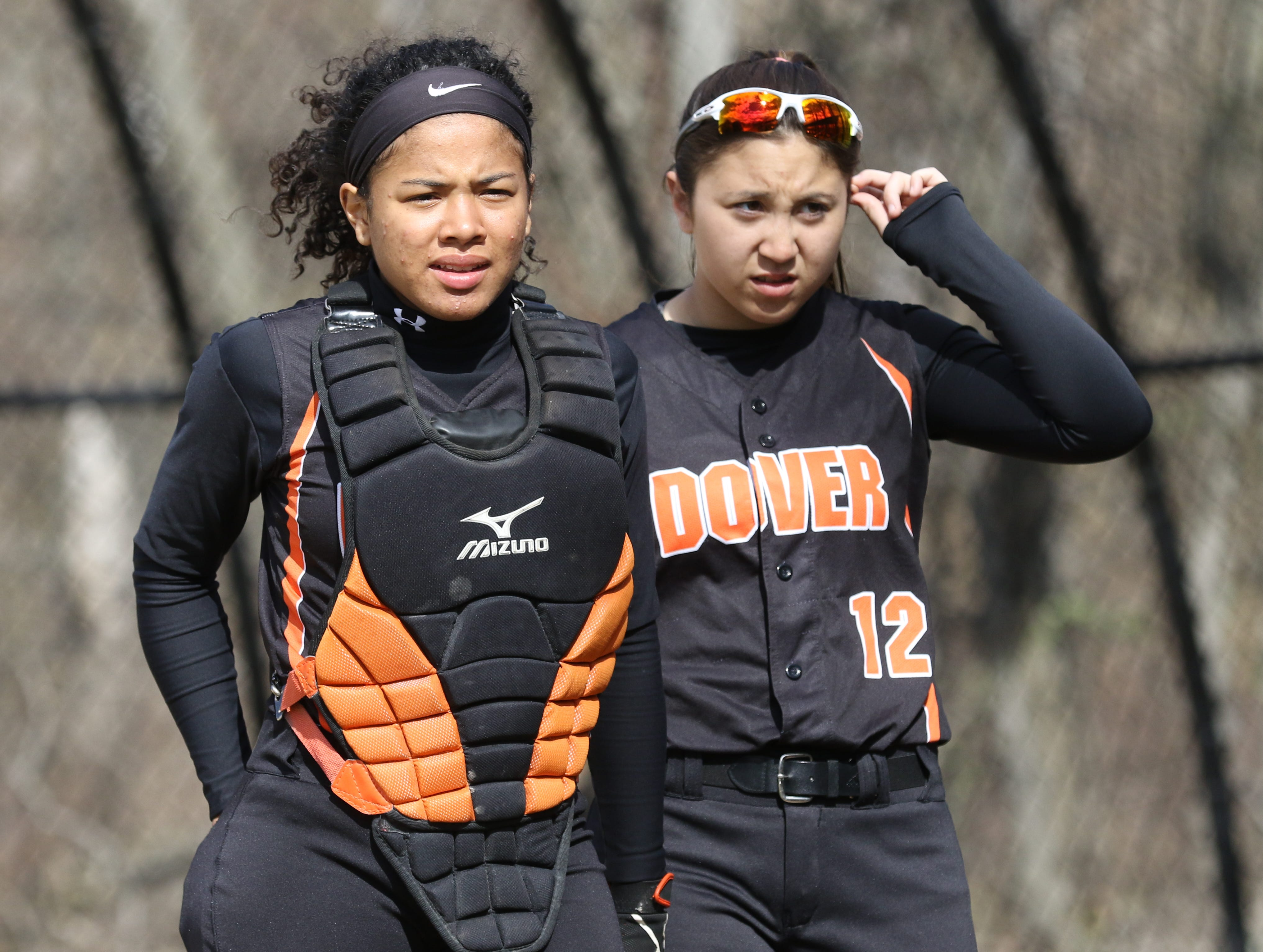 Dover catcher Chelsea Estacio and shortstop Brianna Koo come to the dugout after warmups.