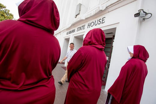 Bianca Cameron-Schwiesow, from left, Kari Crowe and Margeaux Hartline, dressed as handmaids, take part in a protest against HB314, the abortion ban bill, at the Alabama Statehouse in Montgomery, Ala., on Wednesday April 17, 2019.