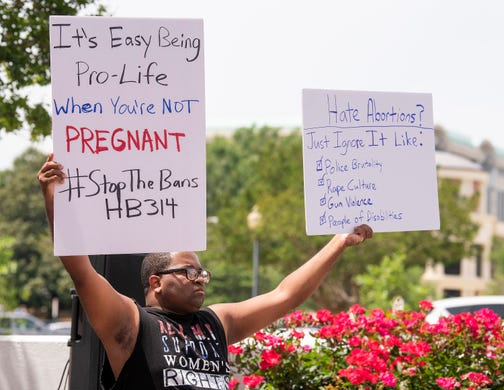 Travis Jackson holds signs during a protest against HB314, the abortion ban bill, at the Alabama Statehouse in Montgomery, Ala., on Wednesday April 17, 2019.