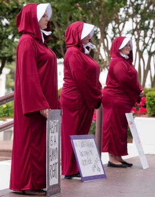 Margeaux Hartline, from left,Kari Crowe and  Bianca Cameron-Schwiesow, dressed as handmaids, take part in a protest against HB314, the abortion ban bill, at the Alabama Statehouse in Montgomery, Ala., on Wednesday April 17, 2019.