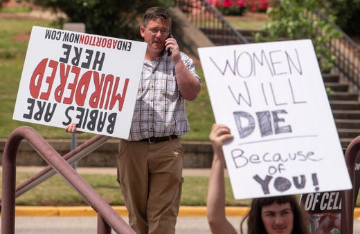A lone anti-abortion protestor protests the protest against  HB314, the abortion ban bill, at the Alabama Statehouse in Montgomery, Ala., on Wednesday April 17, 2019.