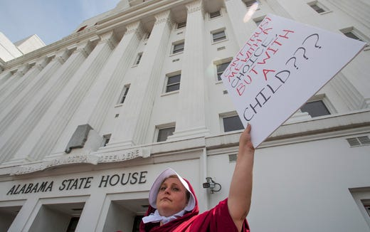 Bianca Cameron-Schwiesow, dressed as a handmaid, takes part in a protest against HB314, the abortion ban bill, at the Alabama Statehouse in Montgomery, Ala., on Wednesday April 17, 2019.