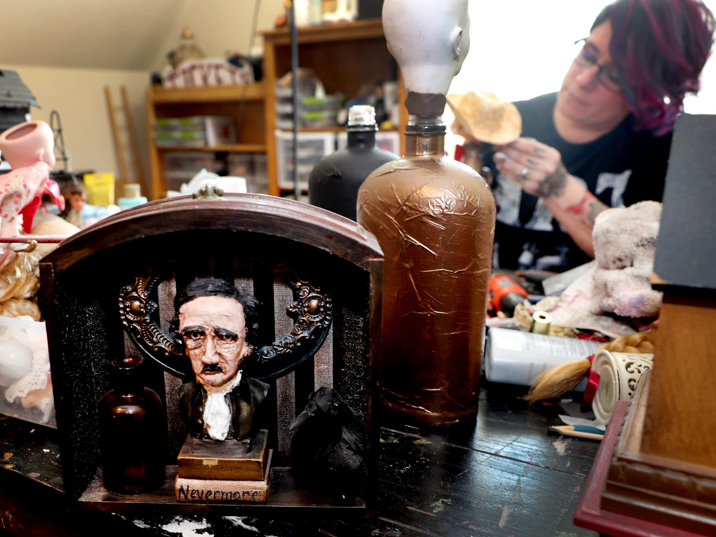 Michelle Sweatt's 3-D piece featuring Edgar Allan Poe can be seen in the foreground as she works on a new piece in the background in her home studio on Tuesday April 16, 2019.