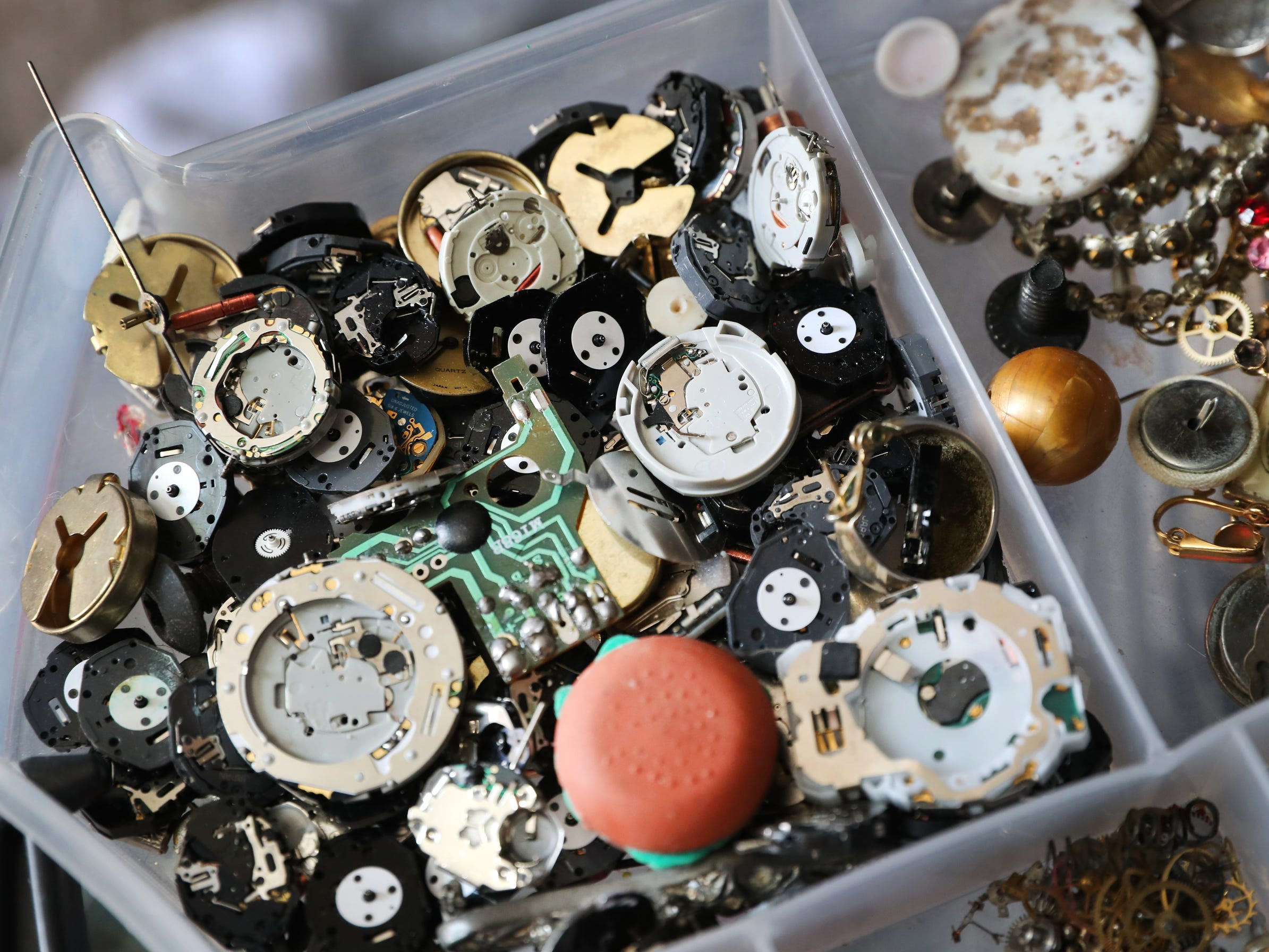 Watch parts are stored in a bin in Michelle Sweatt's home studio on Tuesday April 16, 2019. The pieces are used to create her work since time is a common element in her artwork.