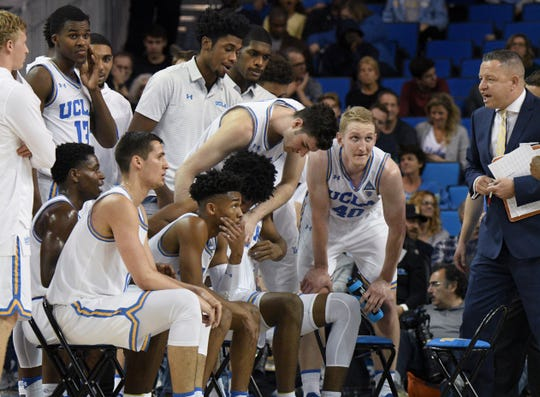 UCLA assistant coach David Grace, right, talks toplayers during a timeout  against Washington State on Dec. 29, 2017.