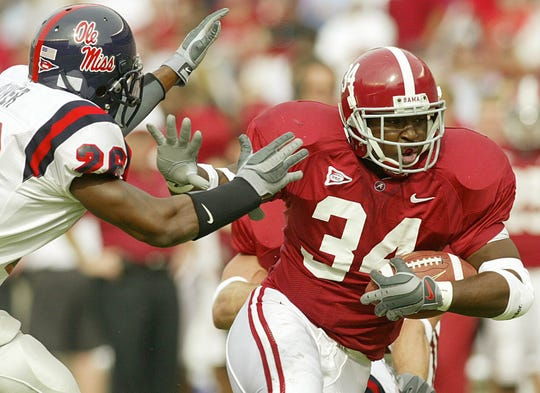 Alabama's Santonio Beard (34) powers up the field against Ole Miss defensive back Eric Oliver (26) for a touchdown on Oct. 19, 2002.