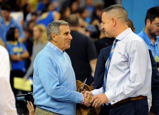 Jim Harrick, left, who coached UCLA's 1994-95 national championship team, greets UCLA assistant coach David Grace on Jan. 19, 2017.