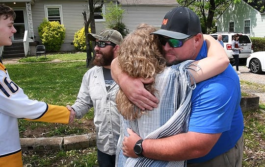 Nashville Electric Service lineman John Harris gets a hug from Tricia Bessow, as she thanks the five NES workers who tried to save her husband with CPR.