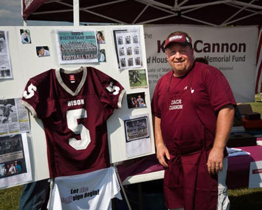 Station Camp High School Coach David Cannon stands by the jersey and tribute display for his late son Kyle Cannon who died in 2011 while serving in the military.