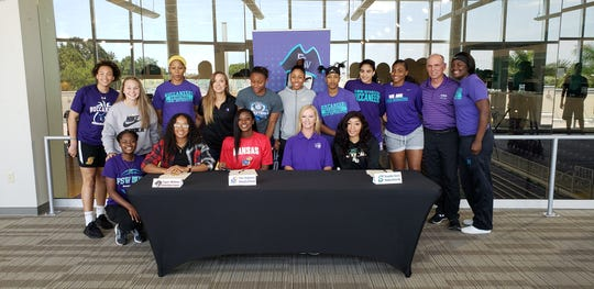 The FSW women's basketball team stands behind teammates Taylor Williams (seated left), Tina Stephens (seated red shirt), coach Kristie Ward (seated purple shirt) and Tonysha Curry (seated right) during a signing ceremony on Wednesday, April 17, 2019. Williams signed with Church Brothers, Stephens with Kansas, and Curry with Stetson.