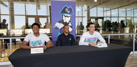 FSW basketball players DeShawn Thomas (left) and Maddox Daniels (right) sit with Bucs' coach Eric Murphy at a signing ceremony on Wednesday, April 17, 2019. Thomas will play at Winthrop next season, while Daniels is headed to Colorado.