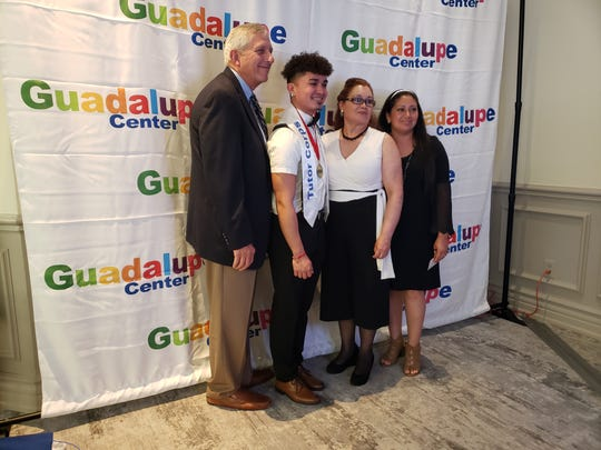 Immokalee High School senior and Guadalupe Center Tutor Corps graduate Jesus Galvan, second from left, takes a picture Tuesday, April 16, 2019, at a photo booth with his mother, Ana Galvan, second from right; his older sister, Ana Luna, right; and his mentor Roger Nolan, far left.