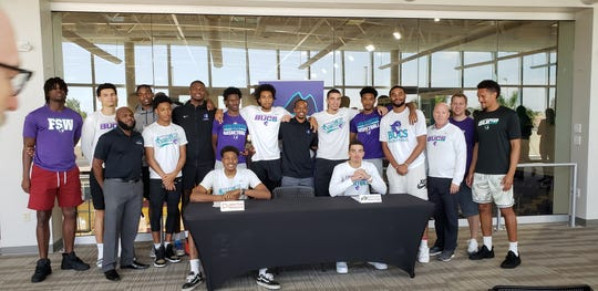 The FSW men's basketball team stands behind teammates DeShawn Thomas (seated left) and Maddox Daniels (seated right) during a signing ceremony on Wednesday, April 17, 2019. Thomas signed to play for Winthrop next year while Daniels committed to Colorado.