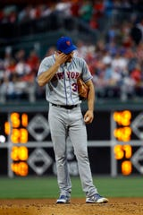 New York Mets' Steven Matz wipes his face after hitting Philadelphia Phillies' Bryce Harper with a pitch during the first inning of a baseball game, Tuesday, April 16, 2019, in Philadelphia.